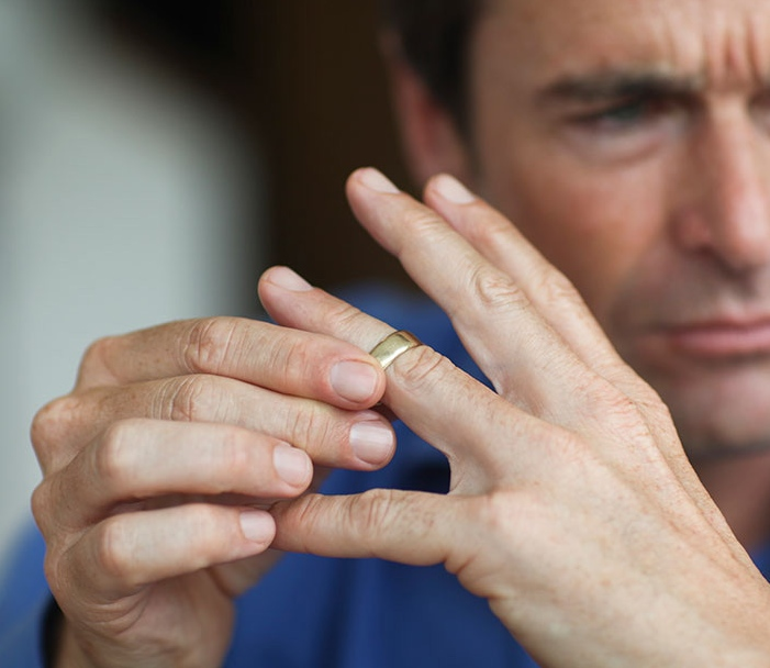 Mature-man-toying-with-gold-wedding-ring-on-finger